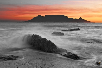 The colors of Table Mountain at sunset with large rock in foreground