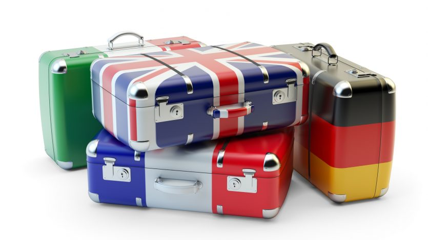 Travel destination and journey luggage concept, stack of suitcases in colors of national flags of european countries isolated on white background