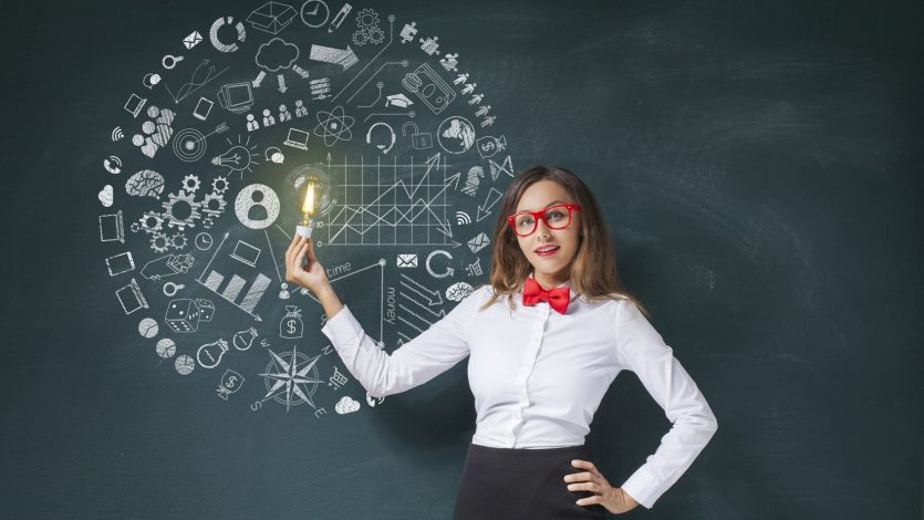 Businesswoman holding lightbulb and business concept icons on blackboard